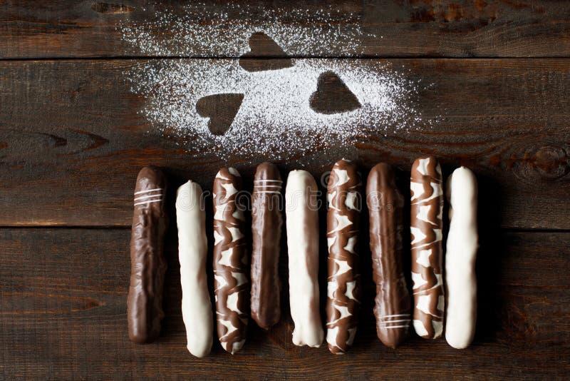 As cookies do chocolate com açúcar pulverizam corações na obscuridade imagem de stock royalty free
