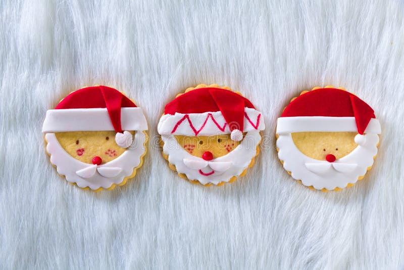As cookies do Natal com Santa enfrentam no fundo branco da pele imagem de stock royalty free