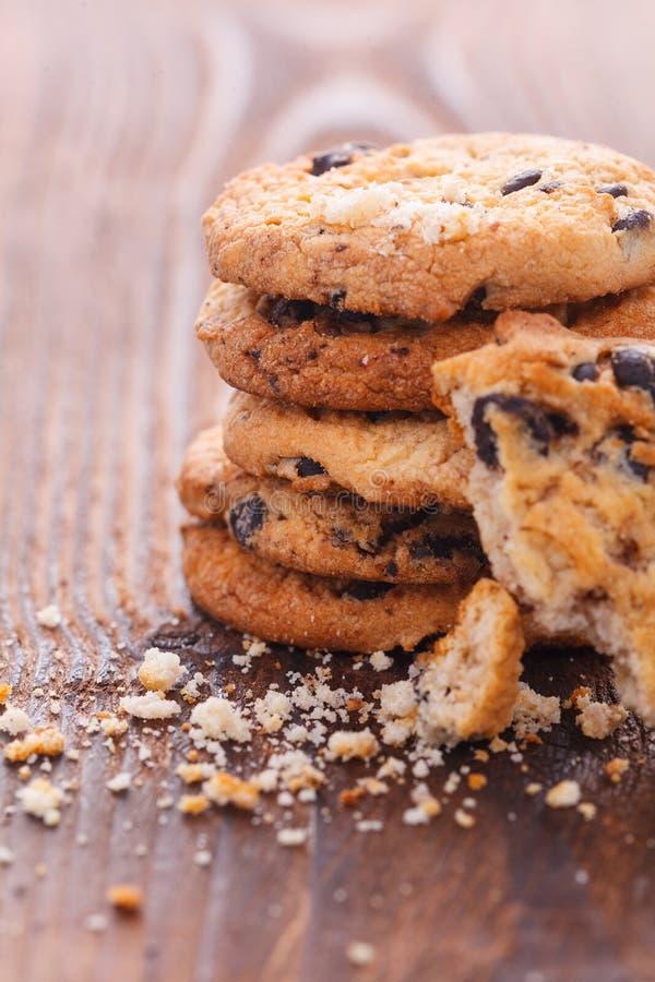 As cookies dos pedaços de chocolate na tabela de madeira velha escura cozeram recentemente Foco seletivo fotografia de stock