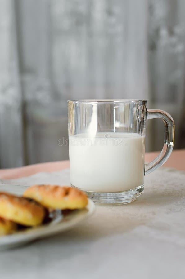 As cookies e o leite estão em uma toalha de mesa branca foto de stock