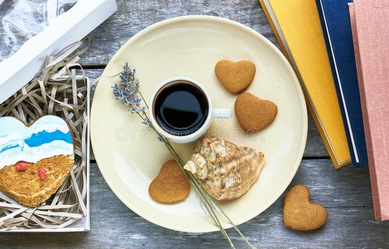 As cookies, o café, a alfazema, o escudo e os livros dados forma coração são próximos na tabela de madeira foto de stock royalty free
