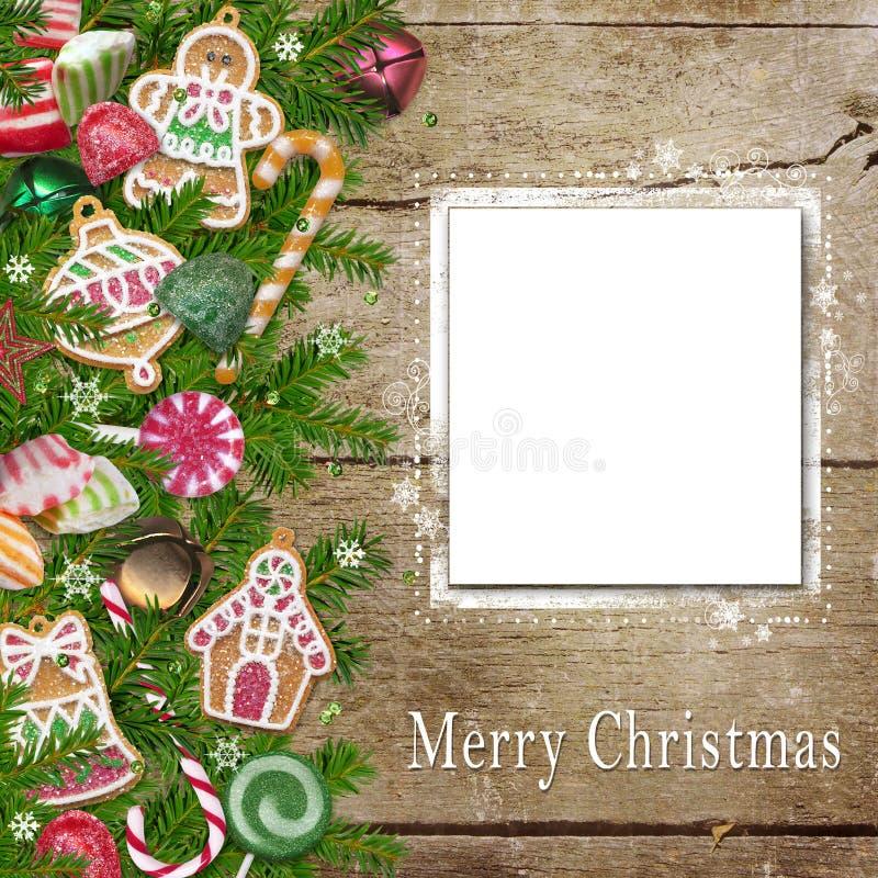 As cookies, os doces, o cartão com lugar para o texto ou a foto do Natal, pinho ramificam em um fundo de madeira ilustração royalty free