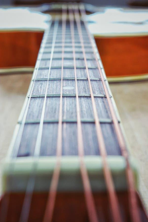 As cordas da guitarra acústica na tabela de madeira na sala, no fim acima da vista superior e na luz solar com espaço vazio para  imagens de stock royalty free