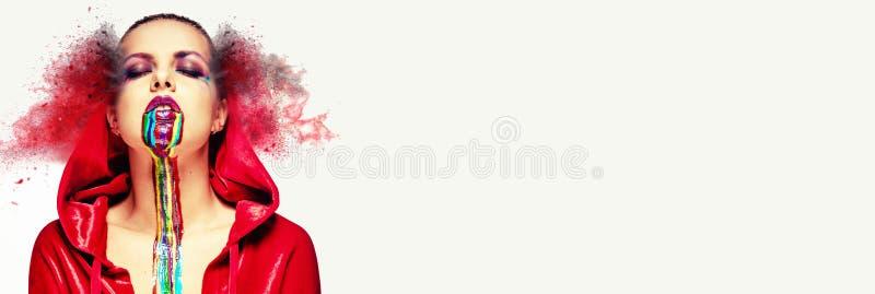 As cores brilhantes criativas do arco-íris da pintura da arte corporal da composição da cara do casaco vermelho 'sexy' do desgast imagens de stock royalty free