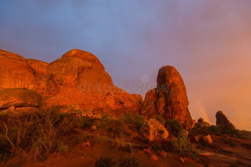 As cores dramáticas, as nuvens e a chuva do por do sol no parque nacional dos arcos abandonam fotos de stock royalty free