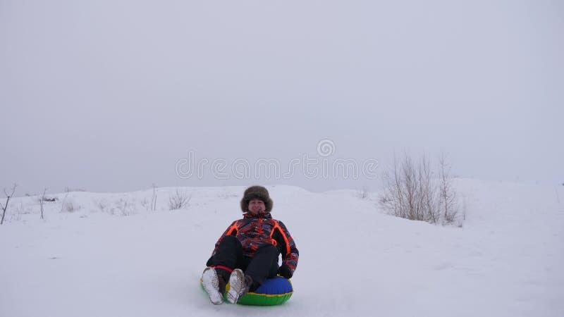 As corrediças felizes do homem da neve alta deslizam um tubo inflável da neve jogo da pessoa no inverno no parque no Natal foto de stock royalty free