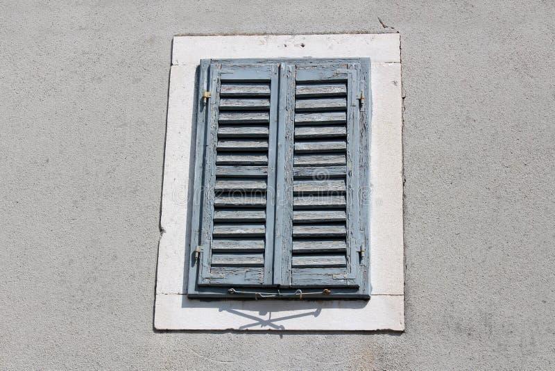 As cortinas de janela de madeira azuis velhas com dilapidado racharam as dobradiças desvanecidas da pintura e do metal montadas n foto de stock