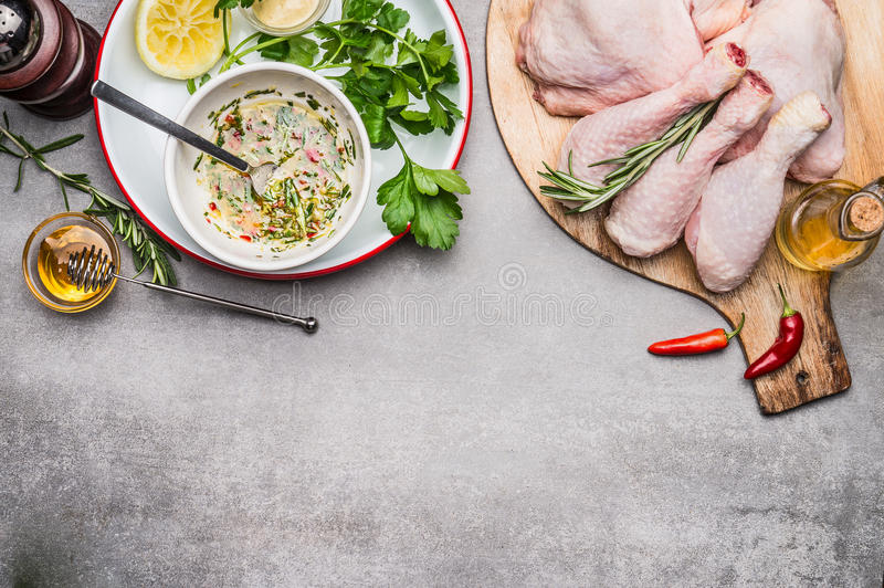 As coxas de frango temperam a colocação em conserva com azeite, mel, ervas e limão, vista superior imagens de stock
