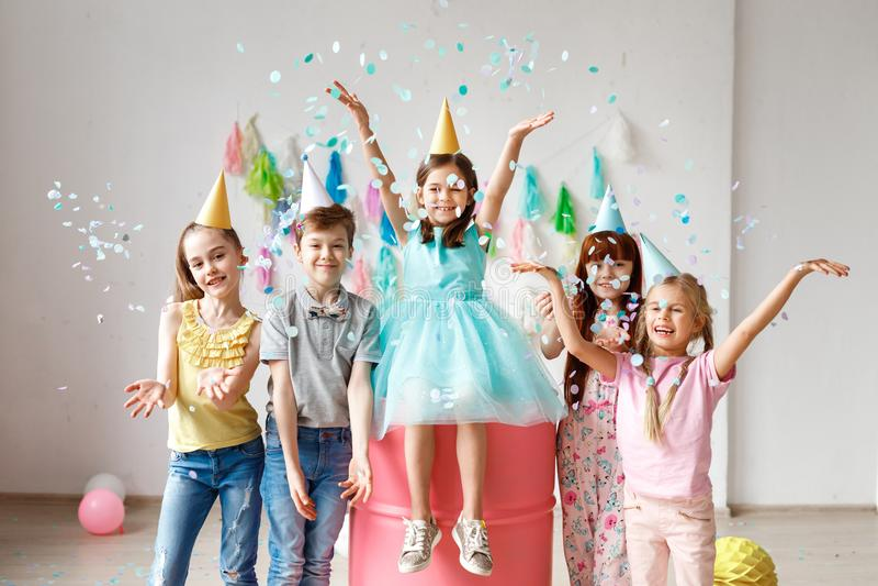 As crianças adoráveis têm o divertimento junto, jogam confetes coloridos, vestem chapéus do cone, têm o divertimento na festa de  imagem de stock