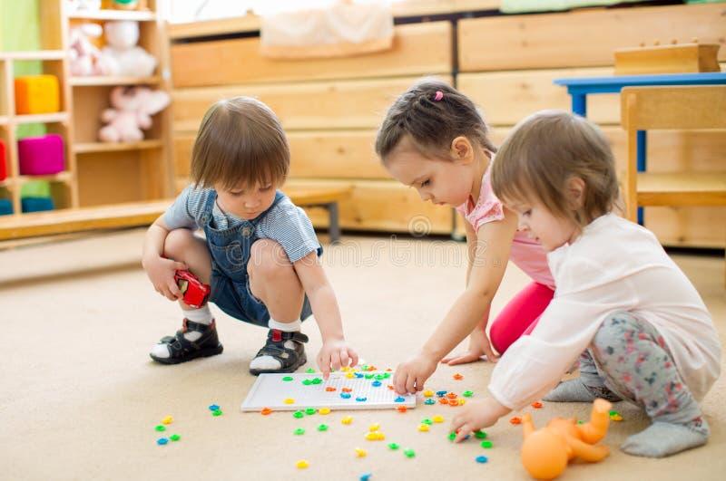 As crianças agrupam o jogo do jogo do mosaico no jardim de infância imagens de stock