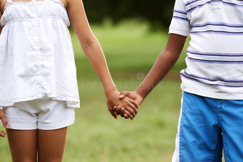 As crianças amam a menina branca do menino preto que guarda as mãos imagens de stock