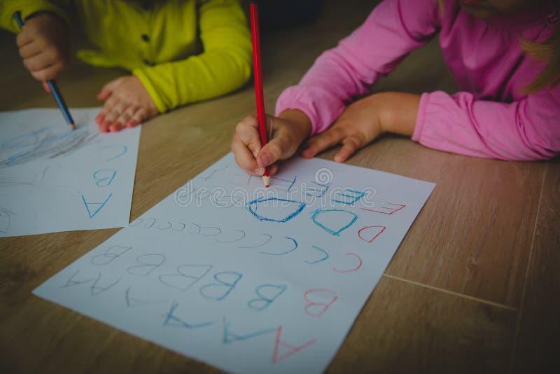 As crianças aprendem escrever letras, alfabeto, fazem trabalhos de casa foto de stock royalty free