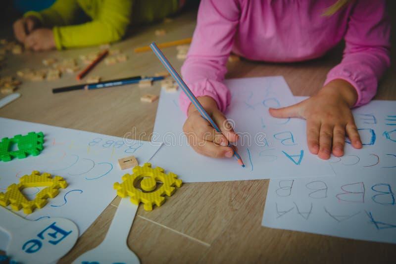 As crianças aprendem escrever letras, alfabeto, fazem trabalhos de casa foto de stock