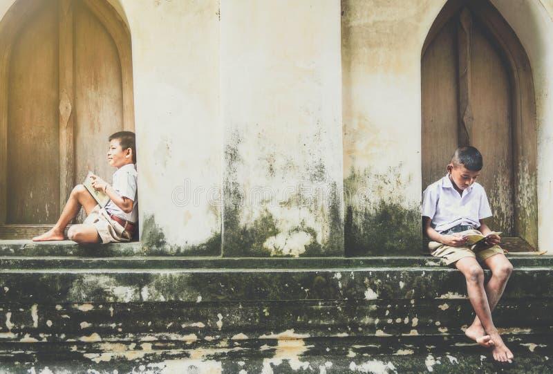 As crianças asiáticas em áreas rurais apreciam sua vida local calma imagem de stock