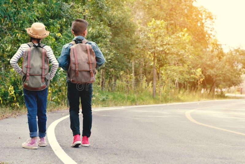 As crianças asiáticas felizes backpack no fundo da estrada e da floresta foto de stock