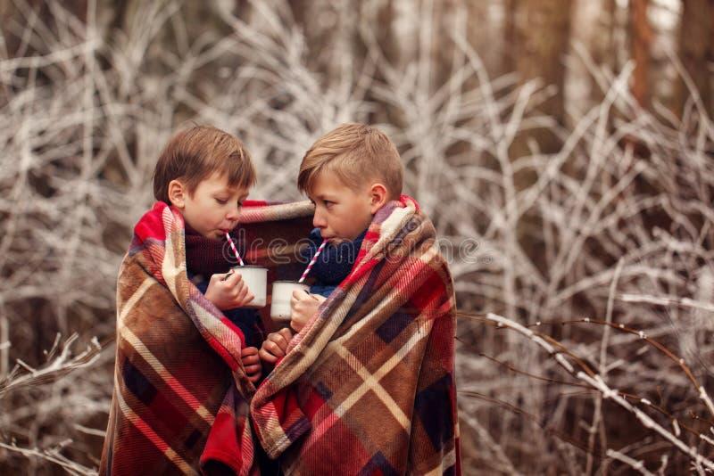 As crianças bebem o chocolate quente sob a cobertura morna em férias do Natal da floresta do inverno imagem de stock royalty free