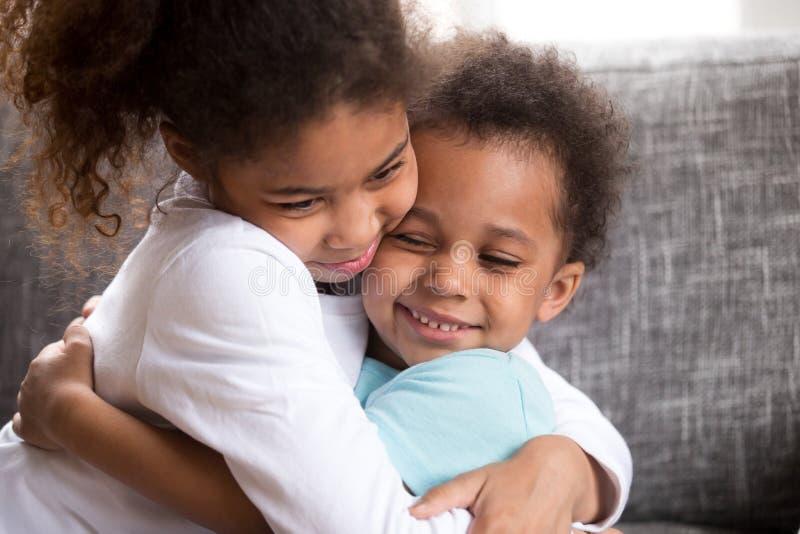 As crianças bonitos da raça misturada abraçam a fatura da paz em casa imagem de stock