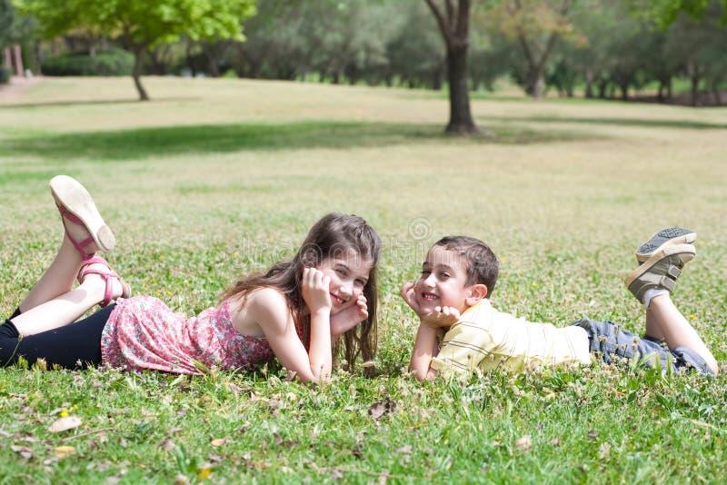 As crianças bonitos encontram-se para baixo na grama verde imagens de stock royalty free