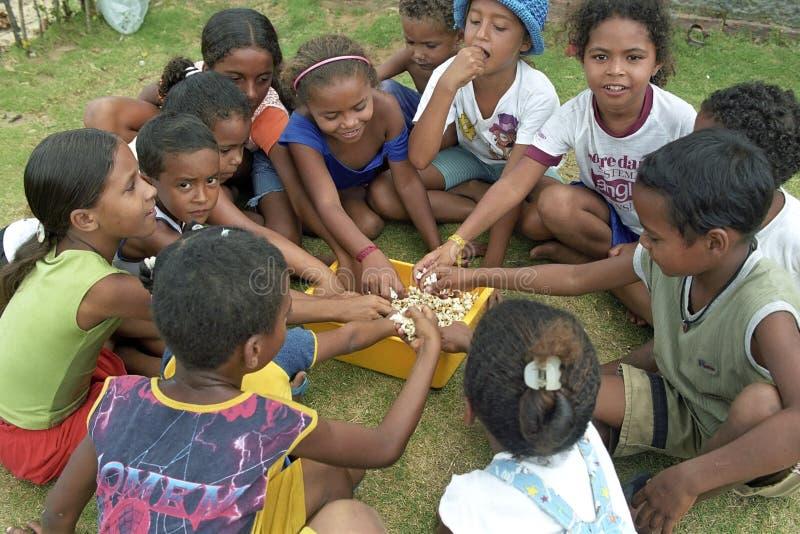 As crianças brasileiras sentam-se junto para comer doces foto de stock royalty free