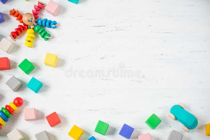 As crianças brincam blocos de madeira do quadro, polvo, carro, pyramidion no fundo de madeira branco Configuração lisa Copie o es imagens de stock