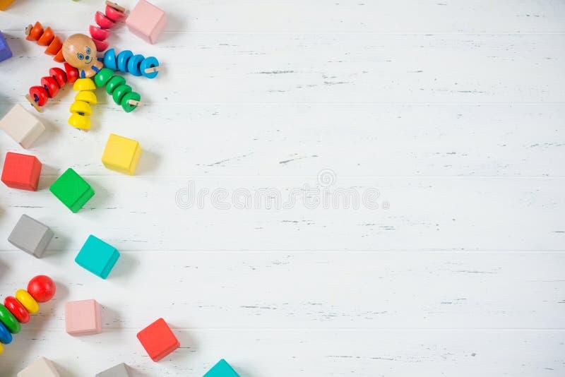 As crianças brincam blocos de madeira do quadro, polvo, pyramidion no fundo de madeira branco Configuração lisa Copie o espaço pa imagens de stock royalty free