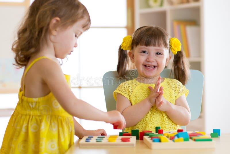 As crianças caçoam o jogo com os brinquedos educacionais, arranjando e classificando cores e formas Aprendizagem através da conce fotografia de stock royalty free