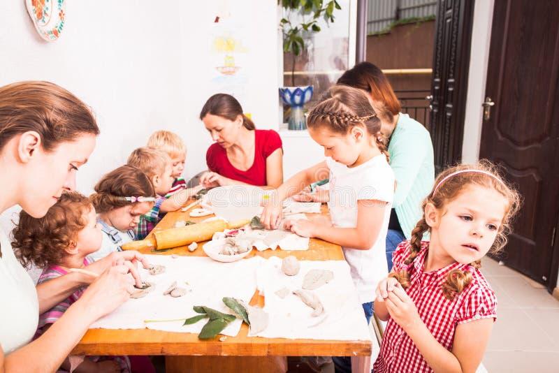As crianças com mães são esculpem fotografia de stock