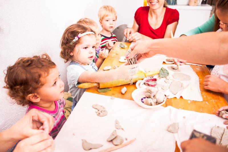 As crianças com mães são esculpem fotos de stock