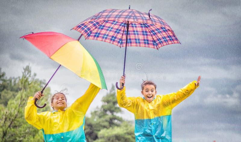 As crianças com o guarda-chuva colorido do arco-íris, as capas de chuva e as botas impermeáveis saltam na chuva imagem de stock royalty free
