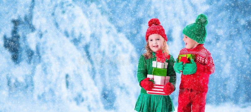 As crianças com presentes de Natal no inverno nevado estacionam fotos de stock royalty free