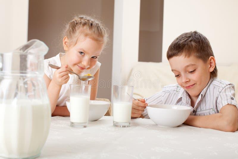 As crianças comem cereais com leite imagem de stock royalty free