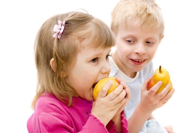 As crianças comem peras imagens de stock