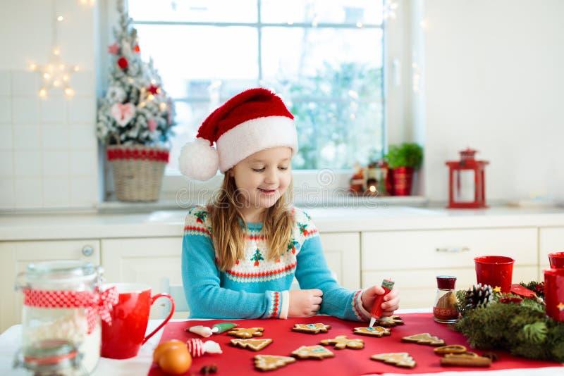 As crianças cozem cookies do Natal Criança no chapéu de Santa que cozinha, decorando o homem de pão-de-espécie para a celebração  fotos de stock