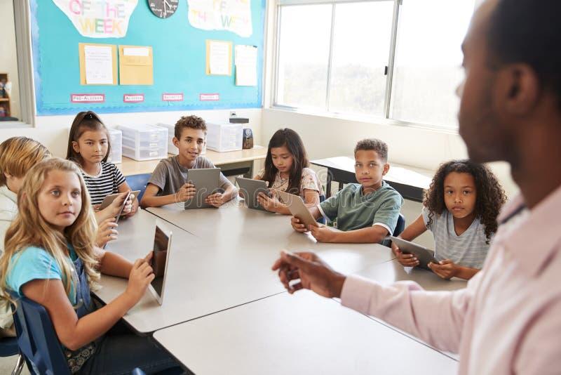 As crianças da escola aprendem usar tabuletas na lição da escola primária foto de stock