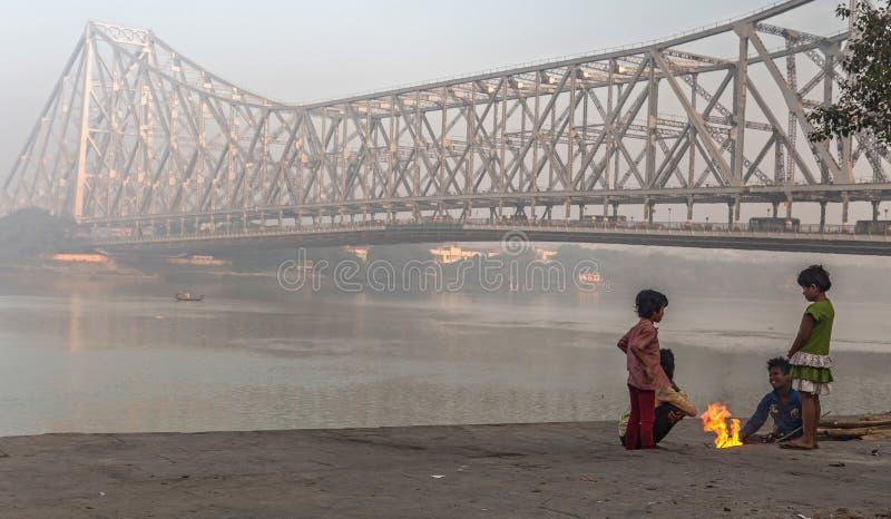 As crianças da rua mantêm-se morno em uma manhã nevoenta fria do inverno no ghat de Mallick perto da ponte de Howrah no banco do  foto de stock royalty free