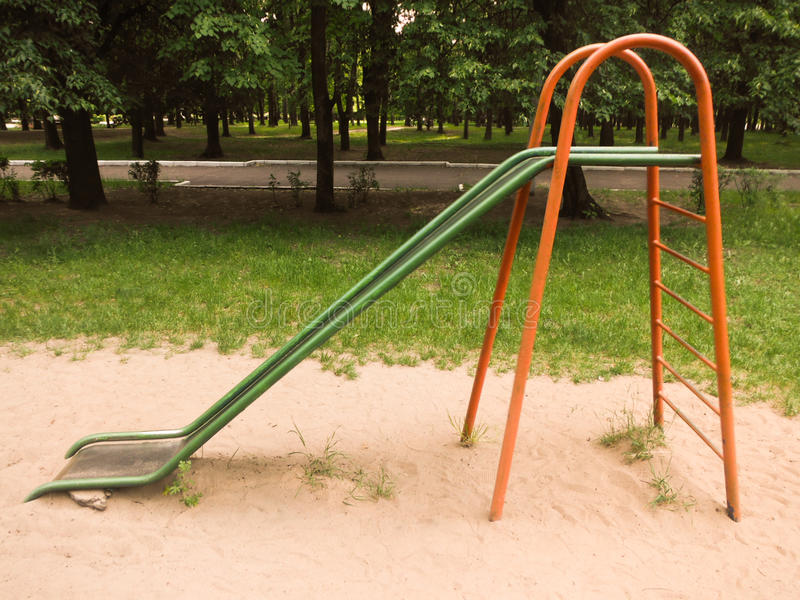 As crianças deslizam no campo de jogos em um parque de diversões fotografia de stock