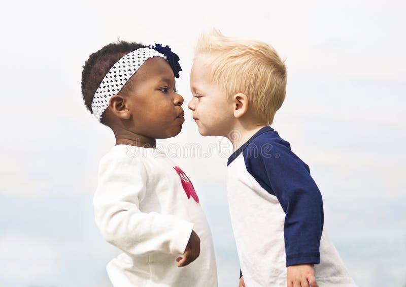 As crianças diversas beijam primeiramente