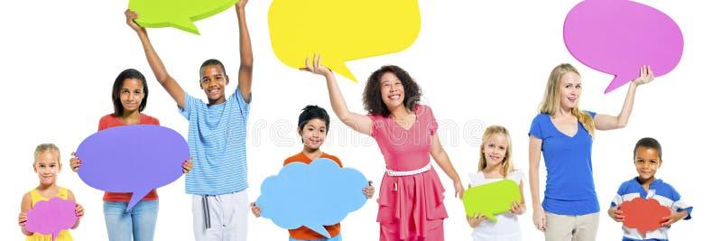 As crianças diversas dos povos do grupo que guardam o discurso borbulham conceito imagens de stock