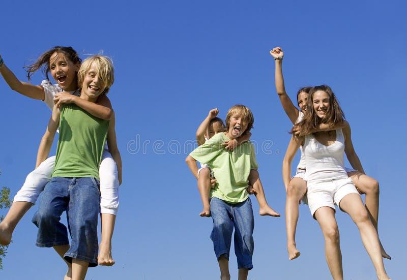 As crianças do grupo andam às cavalitas a raça imagens de stock royalty free