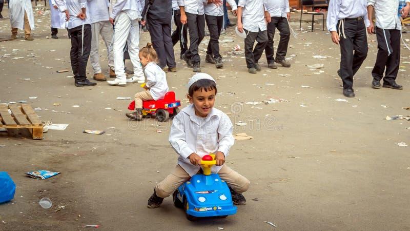 As crianças do hasid do judeu dos peregrinos jogam na rua durante o feriado Há muitos desperdícios ao redor, sujeira Rosh Hashana imagem de stock