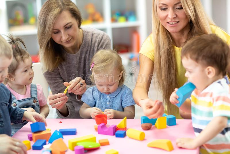 As crianças do jardim de infância jogam com no professor e no professor foto de stock royalty free