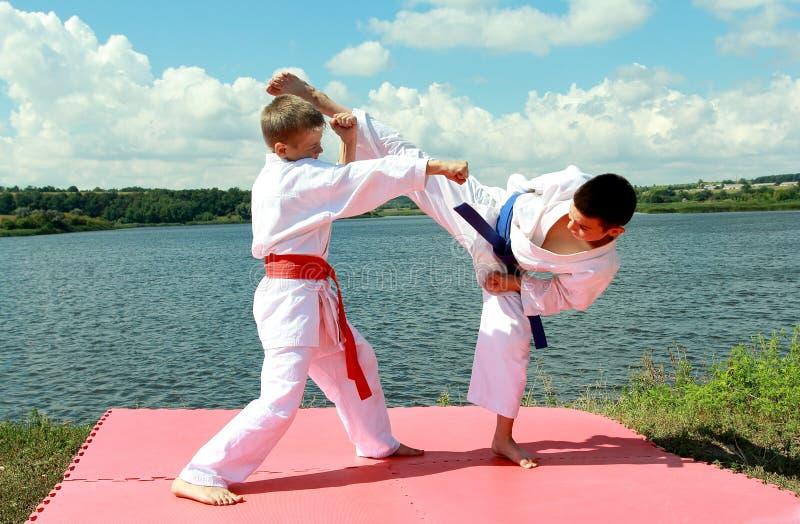 As crianças dos atletas executam o karaté emparelhado dos exercícios imagens de stock royalty free