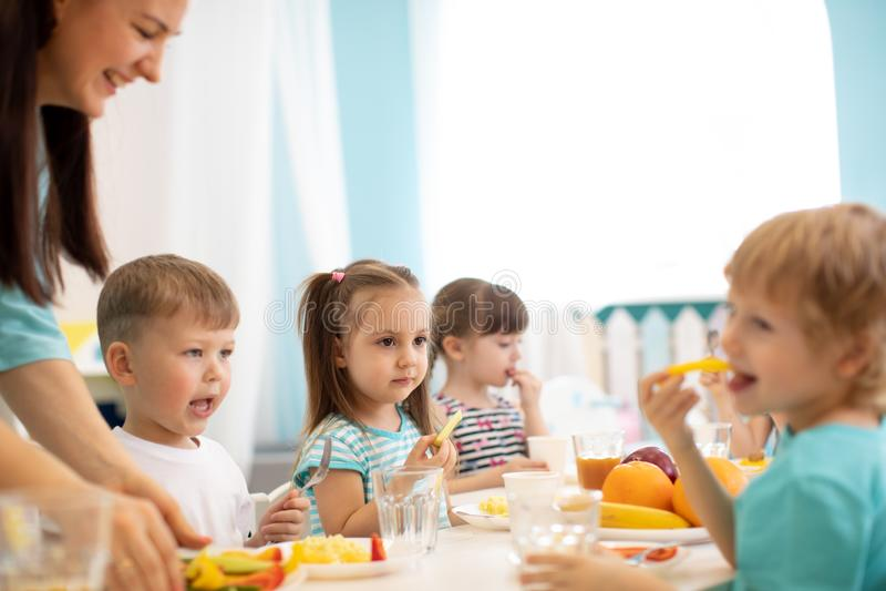 As crianças e a equipe de tratamento comem junto frutas e legumes no jardim de infância ou na guarda fotos de stock