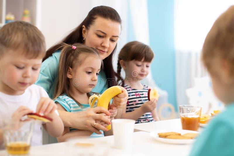 As crianças e a equipe de tratamento comem junto frutos no jardim de infância ou na guarda imagens de stock royalty free
