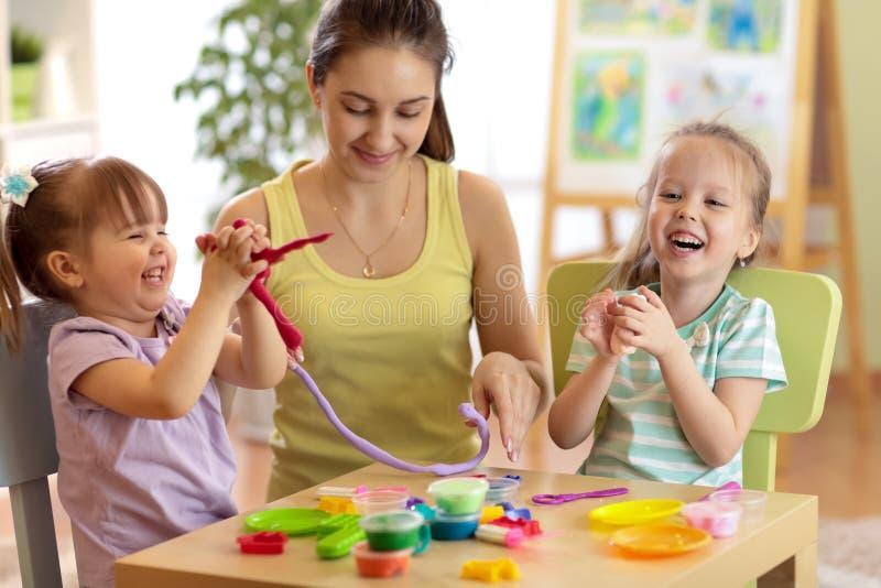 As crianças e a mulher alegres fazem pelas mãos que jogam com massa da cor fotos de stock royalty free