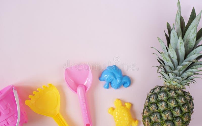 As crianças encalham brinquedos e abacaxi no fundo cor-de-rosa pastel Conceito do ver?o Configura??o lisa, vista superior, espa?o foto de stock royalty free