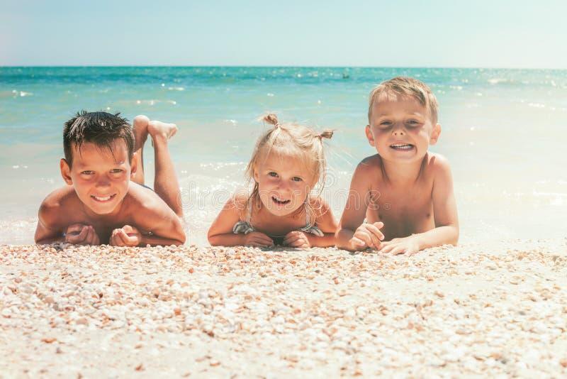 As crianças encontram-se na praia do mar fotos de stock royalty free