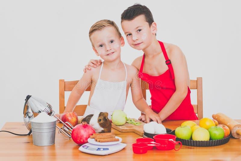 As crianças engraçadas da família feliz estão preparando a torta de maçã, em um fundo branco fotos de stock