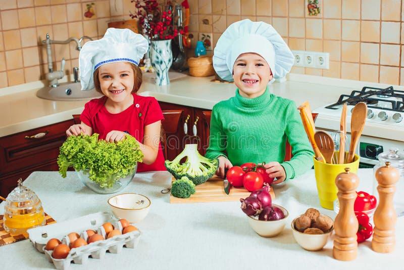 As crianças engraçadas da família feliz estão preparando uma salada do legume fresco na cozinha fotografia de stock royalty free