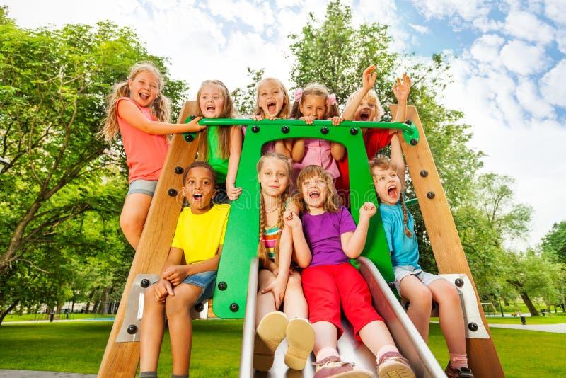 As crianças engraçadas no campo de jogos chute com braços acima foto de stock